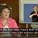 "Screenshot from a captioned video in which a woman is saying, ""This is the first time I had a deaf student and certainly I was a bit anxious about it."" An Australian Sign Language interpreter is shown in the corner of the screen."