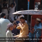 Screenshot from a video telling the story of Asif. Asif, a rickshaw driver, uses gestures to communicate with a customer who is paying him.