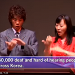 Screenshot from a video on the South Korean Association of the Deaf shows two people signing. English captions are at the bottom of the screen.