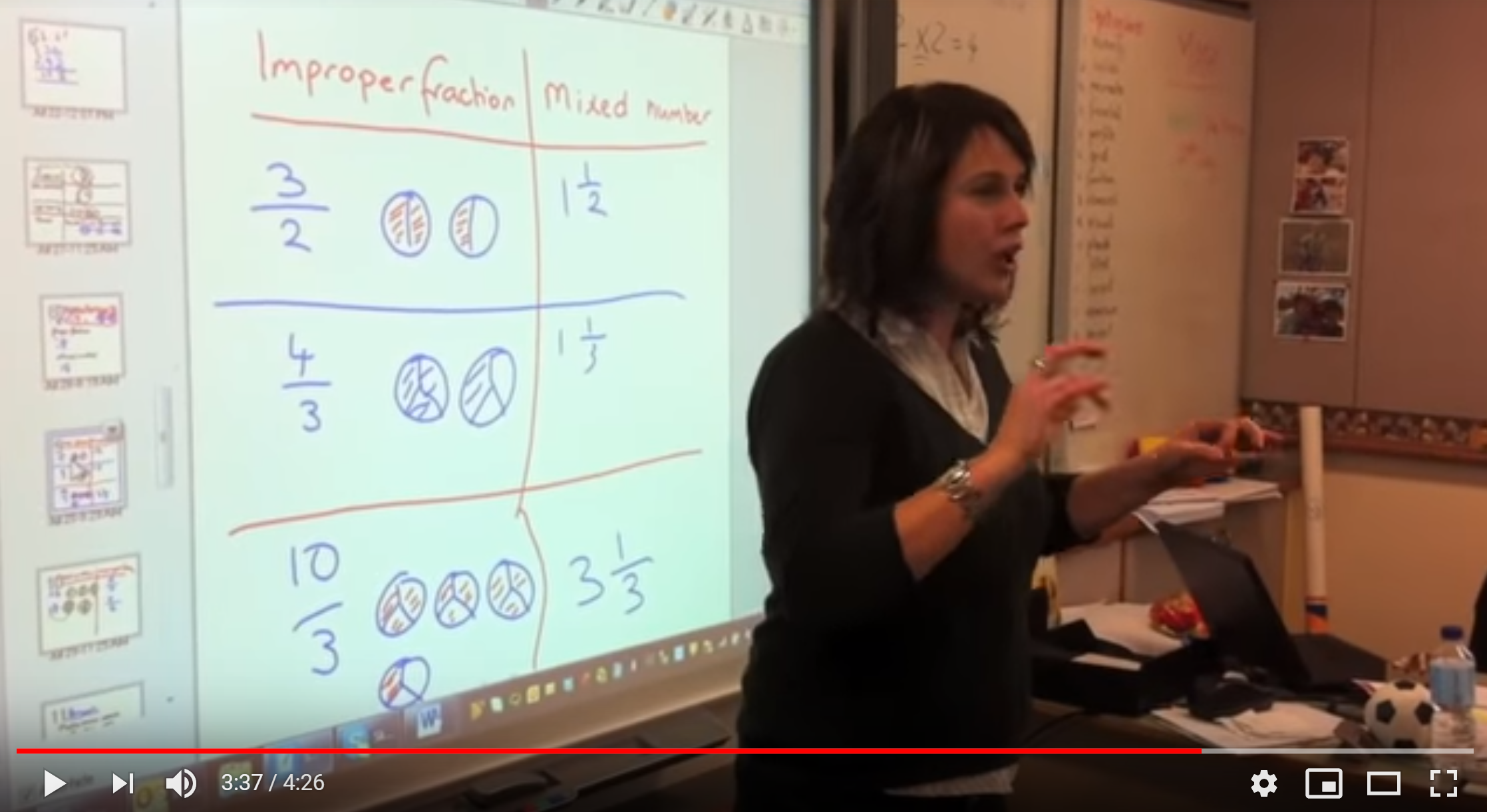 A screenshot of a video that shows a woman in a classroom signing to her students (off camera). Behind her is a projector screen with information about fractions.