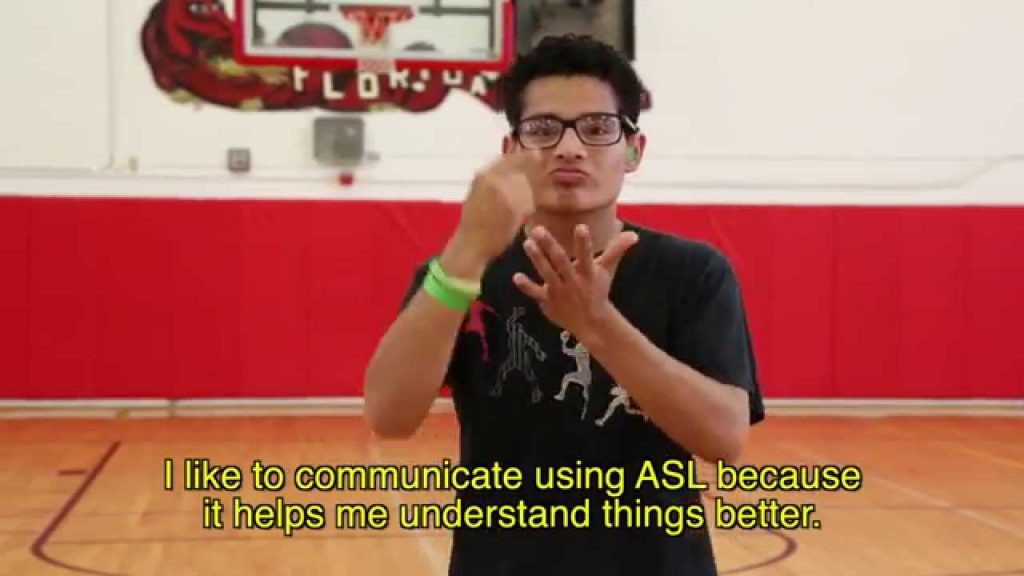 "Screen shot from the video ""What Deaf Students Want in A Teacher"". In this scene, a teenage boy is standing on a basketball court signing to the camera."