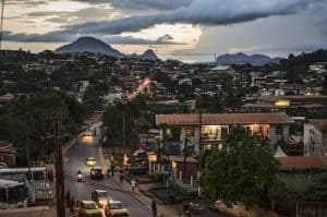 Photo of Yaoundé, Cameroon at dusk. A well lit city street has many low level buildings. In the distance are mountains and a sunset partially covered by clouds.