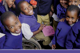 """Screenshot of the publication entitled """"Early Childhood Development and Disability: A discussion paper"""". Above the title is a picture that shows many children clustered together, smiling up at the camera. In the middle, one boy uses a wheelchair."""