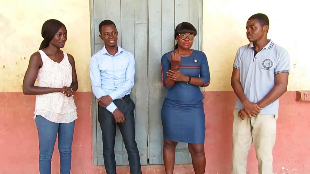 Four people are standing in a row in front of a wall. Some face the camera, some look toward each other.