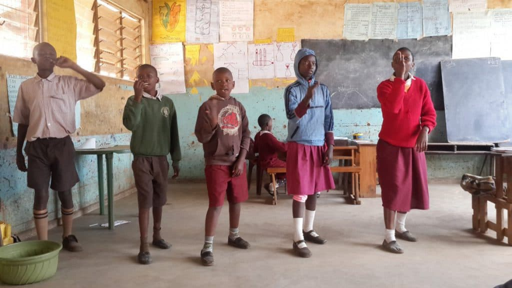 Four school children stand in a classroom reciting poetry in Kenya Sign Language. Another child sits at a desk behind them.