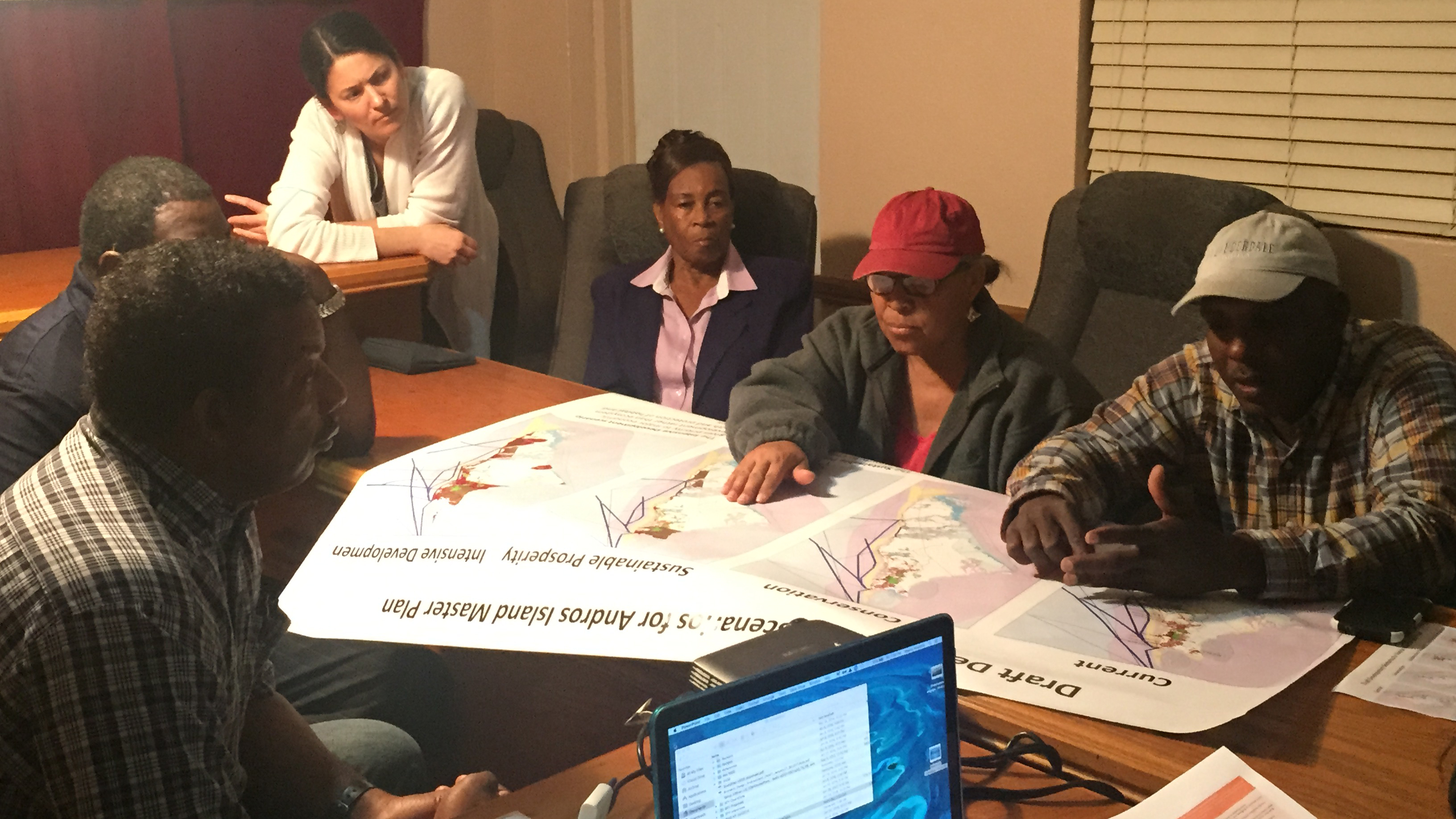 A group of six adults are seated around a table looking together at large sheets of paper.