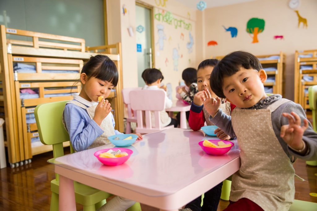 Very young children are seated at tables in a classroom. Each has a snack bowl in front of them.